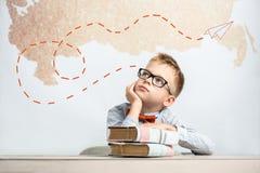 En fundersam skolpojke sitter på ett skrivbord med böcker royaltyfri bild