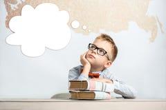 En fundersam skolpojke sitter på ett skrivbord med böcker Royaltyfri Fotografi