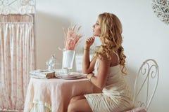 En fundersam stående av en ung blond flicka i en ljus klänning I arkivfoto