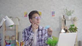 En fundersam ung asiatisk man i stilfulla exponeringsglas arbetar på en bärbar dator och rymmer en kontokort i vardagsrummet av h lager videofilmer