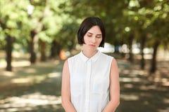 En fundersam ung dam står i en grön sommar parkerar Den härliga damen i en elegant och modern blus går utomhus Royaltyfri Bild