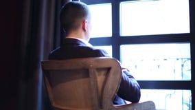 En fundersam ung man sitter på den retro fåtöljen framme av fönstret stock video