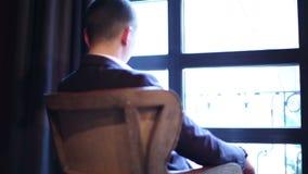En fundersam ung man sitter på den retro fåtöljen framme av fönstret och vikningen hans armar arkivfilmer