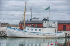 En funktionsduglig fiskebåt i hamnen med dramatisk molnig himmel royaltyfri foto