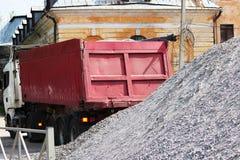 En funktionsduglig lastbil förbereder sig att lasta av grus på platsen för att bygga en parkeringsplats för turist- bussar Övrema Royaltyfri Fotografi