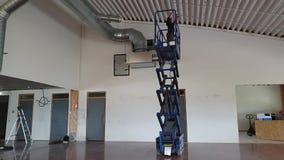 En funktionsduglig man scissor på elevatorfixandetaket Byggnationbegrepp lager videofilmer