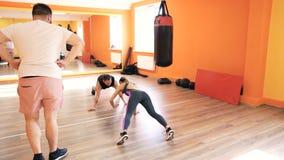 En fyllig grabb och en slank flicka Personlig boxas utbildning i konditionklubba eller idrottshall Styrkaövningar och övning stock video