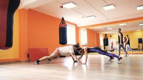 En fyllig grabb och en slank flicka Personlig boxas utbildning i konditionklubba eller idrottshall Styrkaövningar och övning lager videofilmer