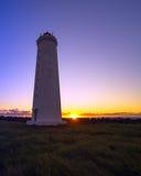 En fyr och en solnedgång Arkivbilder