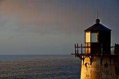 En fyr stirrar av in mot solnedgången arkivbilder