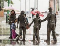 En gå med paraplyer i regnet arkivfoton