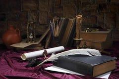 En gåsfjäder, en bläckhorn, en snirkel med en skyddsremsa, en falsk bronsljusstake med en stearinljus, böcker, ett förstoringsgla Arkivfoton