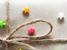 En gåva- eller gåvaask som sloggs in av busebrunt återanvände papper och som band med det bruna hamparepet som band med den mång- Arkivfoton