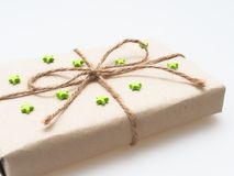 En gåva- eller gåvaask som sloggs in av busebrunt återanvände papper och som band med det bruna hamparepet som band med grön rubb Royaltyfri Foto