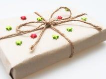 En gåva- eller gåvaask som sloggs in av busebrunt återanvände papper och som band med det bruna hamparepet som band med röd och g Arkivfoto