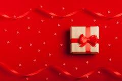 En gåva i en ask på en röd bakgrund Arkivfoto