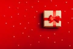 En gåva i en ask på en röd bakgrund Arkivbilder