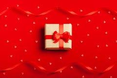 En gåva i en ask på en röd bakgrund Arkivbild