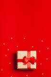 En gåva i en ask på en röd bakgrund Fotografering för Bildbyråer