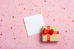 En gåva i en ask på en rosa bakgrund Royaltyfri Bild