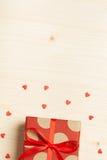En gåva i en ask på en träbakgrund Arkivfoto