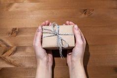 En gåva i händerna av en flicka Framlägga en gåva royaltyfri fotografi