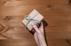 En gåva i händerna av en flicka Framlägga en gåva royaltyfria foton