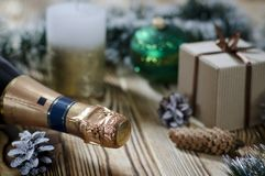 En gåva lägger på en trätabell bredvid en stearinljus, kottar och en ängel mot bakgrunden av julpynt royaltyfri foto