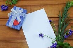 En gåva med blommor och ett ställe för lyckönskan Arkivfoto