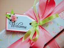 En gåva slågen in ask med det välkomna kortet Ljus - blått papper med gräns - rosa rosor Royaltyfria Foton