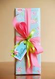 En gåva slågen in ask med det välkomna kortet Ljus - blått papper med gräns - rosa rosor Royaltyfri Foto