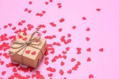 En gåva som slås in i kraft papper på en rosa bakgrund Röda hjärtor på en gåvaask royaltyfria foton