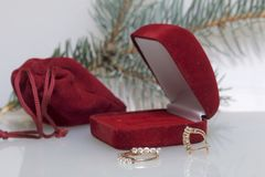 En gåva till älskad En röd påse för sammet och en gåvaask Närliggande är en guld- cirkel och guldörhängen På en vit bakgrund med  Arkivbild