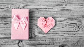 En gåvaask med en pilbåge och en delikat rosa hjärta som göras av papper på en grå bakgrund Vykorthjärta av origami kopiera avstå Fotografering för Bildbyråer