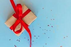 En gåvaask som slås in beautifully med kraft papper och den röda stor pilbågen för band och på blå bakgrund med kopieringsutrymme royaltyfri foto