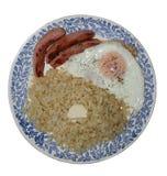 En gachas de avena del bulgur de la placa Huevo frito y salchichas asadas a la parrilla Foto de archivo libre de regalías