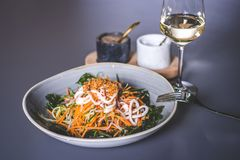 En gaffel ligger på kanten av en platta med en sallad Royaltyfri Foto
