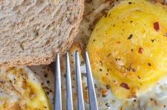 En gaffel som siktar på stekt ägg och rostat bröd med smaktillsats fotografering för bildbyråer
