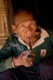 En gamal man av det Akha folkgruppstaget i skuggan av hans bambuhus som röker med ett trärör Arkivbild