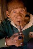 En gamal man av det Akha folkgruppstaget i skuggan av hans bambuhus som röker med ett trärör Royaltyfria Foton