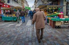 En gamal man går bland grönsak- och fruktställningar i en utomhus- marknad Arkivfoto