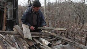 En gamal man går mycket till och med brädena för att reparera en förlägga i barack eller tända brand, liv efter kriget stock video