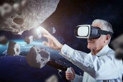 En gamal man har hans yttre rymderfarenhet med en virtuell verklighethörlurar med mikrofon Beståndsdelar av denna avbildar möbler Royaltyfri Foto