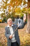En gamal man i en parkera och att vinka hans hand och innehav en mobiltelefon med en monopod arkivbilder
