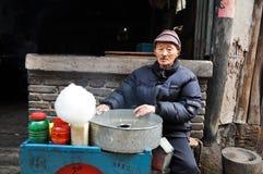 En gamal man och hans sockervadd i Kina Arkivfoto