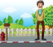 En gamal man på vägrenanseendet nära brevlådan Royaltyfri Bild