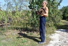 En gamal man utför övningar med en skivstång arkivbilder