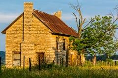 En gamla Abandonded Texas Farmhouse med olika vildblommor Royaltyfri Bild