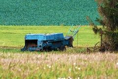 En gammal åkerbruk maskin i landsfältet fotografering för bildbyråer