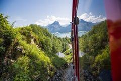 En gammal ångalokomotiv klättrar upp 'schafbergbahnen' på till överkanten av Schafbergen Royaltyfri Fotografi